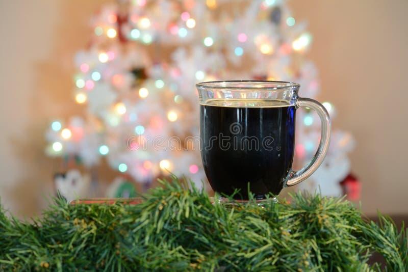Exponeringsglas av varm kakao framme av den vita julgranen med kulöra ljus royaltyfria bilder