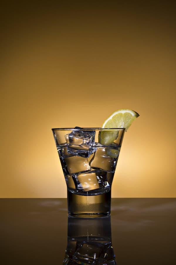 Exponeringsglas av vatten med citron- och iskuber p? bakgrund exponerad i apelsin fotografering för bildbyråer