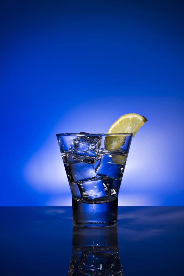 Exponeringsglas av vatten med citron- och iskuber p? bakgrund exponerad i bl?tt royaltyfri fotografi