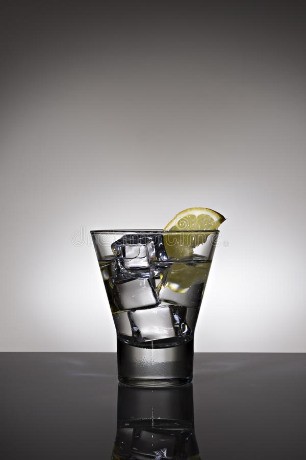 Exponeringsglas av vatten med citron- och iskuber p? bakgrund exponerad i gr? f?rger arkivfoton