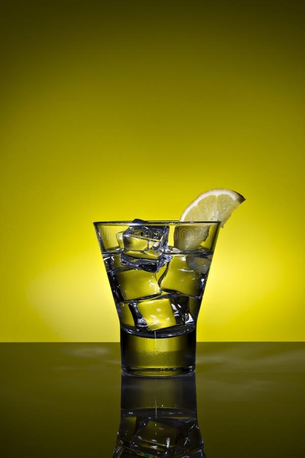 Exponeringsglas av vatten med citron- och iskuber p? bakgrund exponerad i guling arkivfoto
