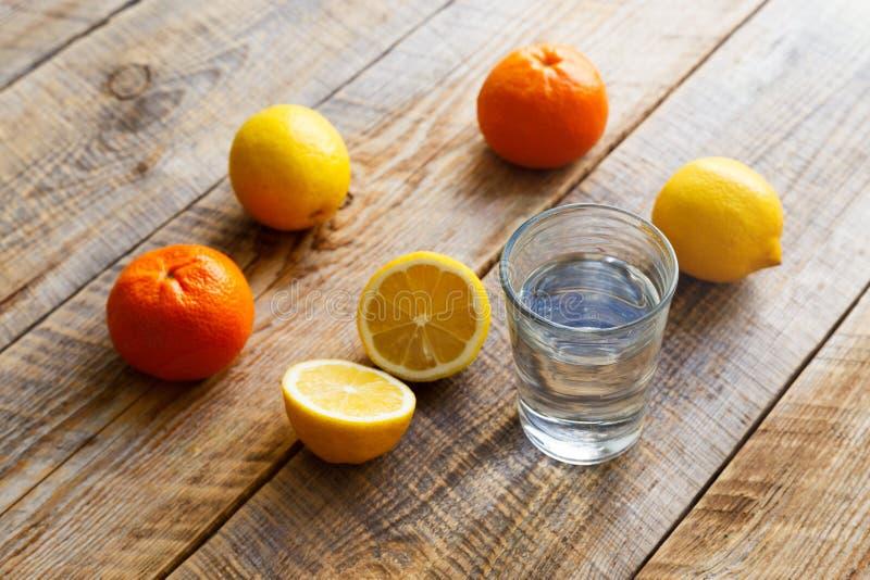 Exponeringsglas av vatten med citronen och apelsiner på trätabellen royaltyfria foton
