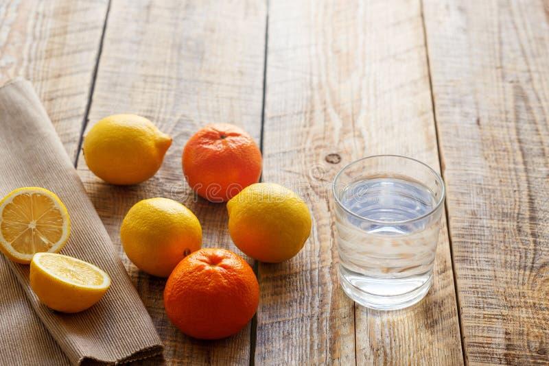 Exponeringsglas av vatten med citronen och apelsiner på trätabellen royaltyfri foto
