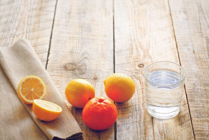 Exponeringsglas av vatten med citroner och apelsiner på trätabellen arkivfoto