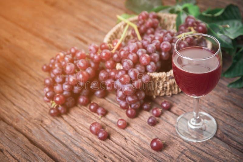 Exponeringsglas av vin eller druvafruktsaft och frukt på trätabellen fotografering för bildbyråer