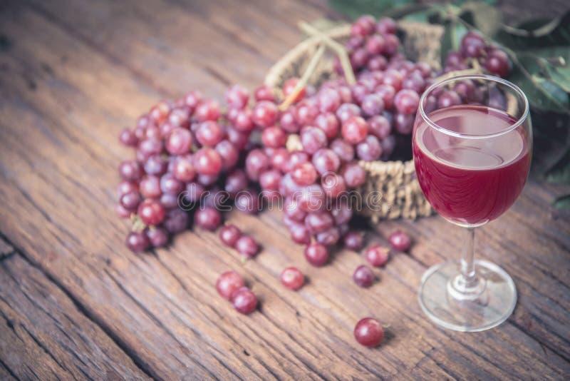 Exponeringsglas av vin eller druvafruktsaft och frukt på trätabellen royaltyfri fotografi