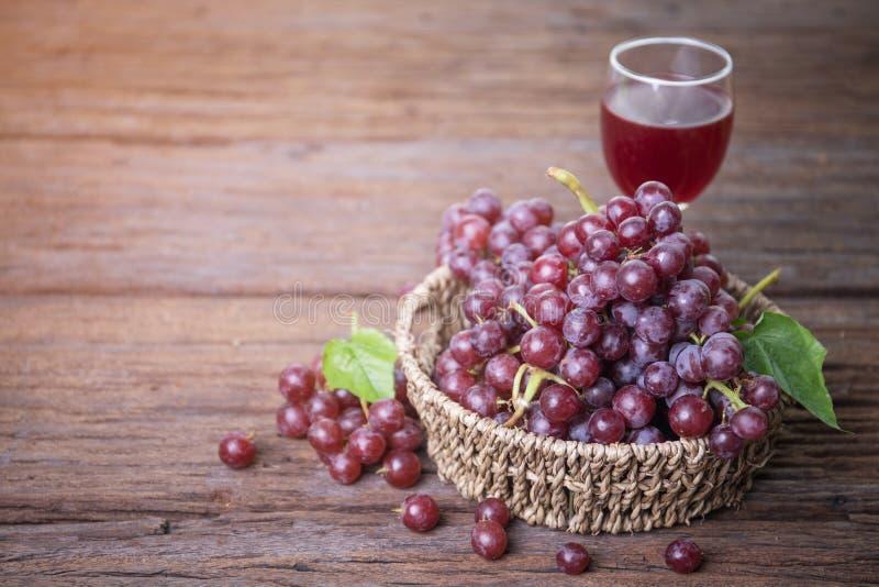 Exponeringsglas av vin eller druvafruktsaft och frukt på trätabellen arkivbild