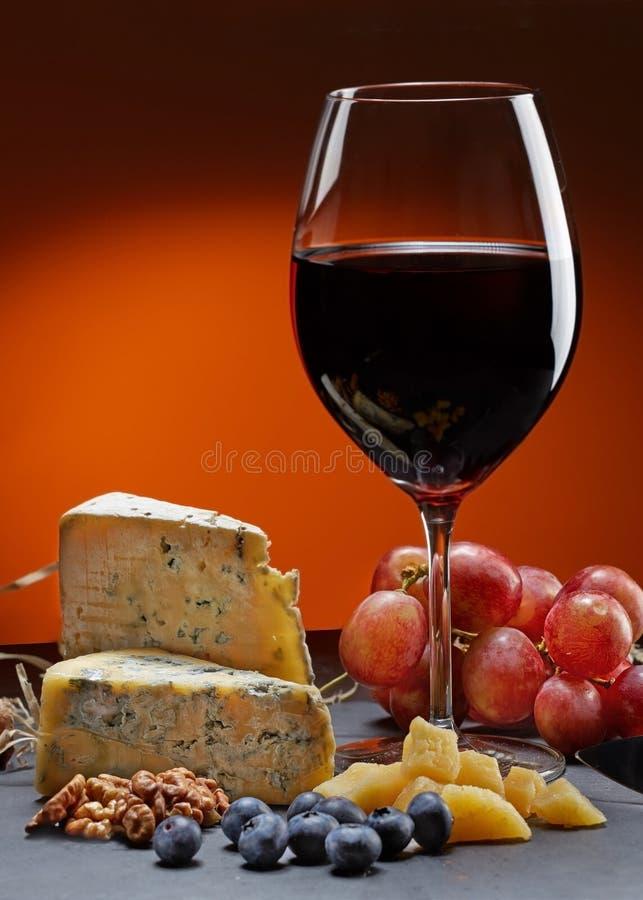 Exponeringsglas av vin med druvor och ett stycke av ost med formen valnötter, parmesanost och blåbär arkivbild