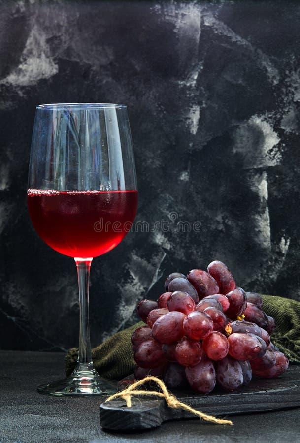 Exponeringsglas av vin med druvor p? en svart tr?st?llning royaltyfri bild