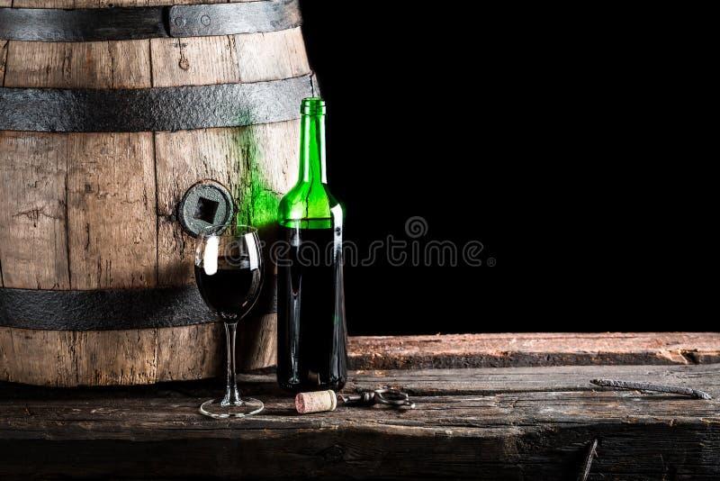Exponeringsglas av vin med flaskan och den gamla eken barrel royaltyfria bilder