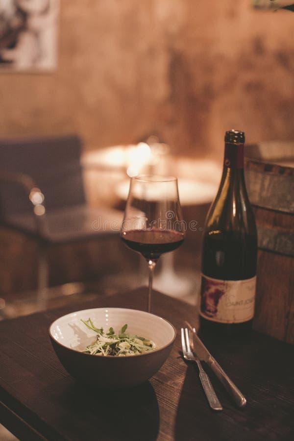 Exponeringsglas av vin med sallad i restaurangen fotografering för bildbyråer