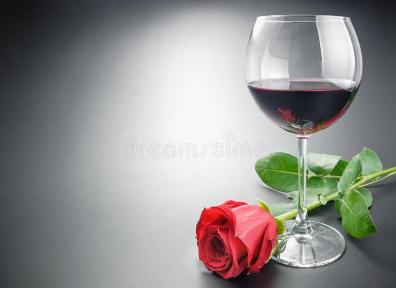 Exponeringsglas av vin- och rosblomman royaltyfri bild