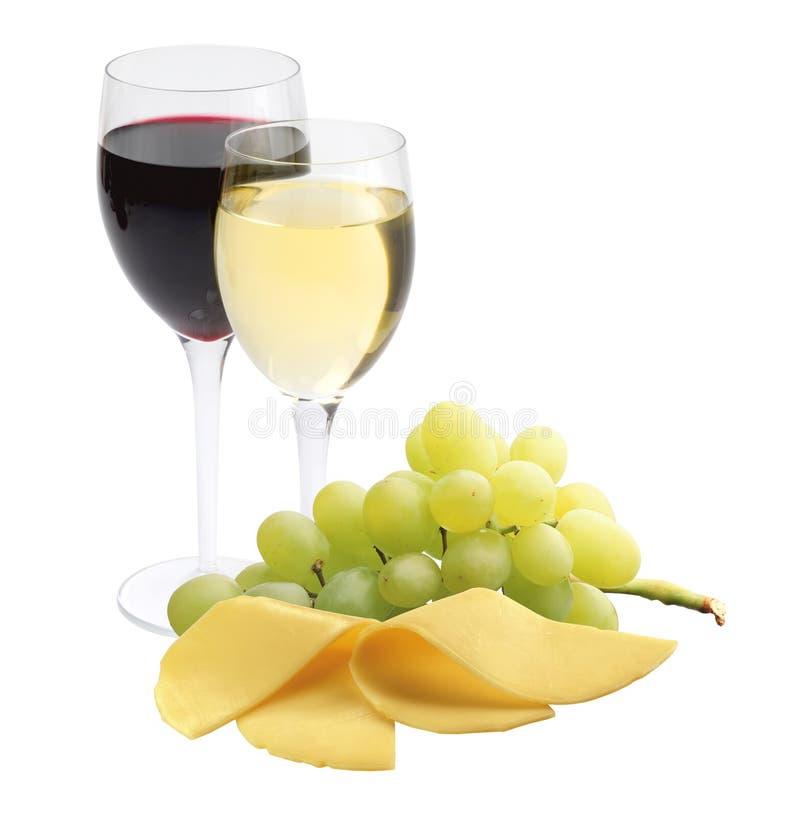 Exponeringsglas av vin, ost och mogna druvor som isoleras på vit royaltyfria bilder
