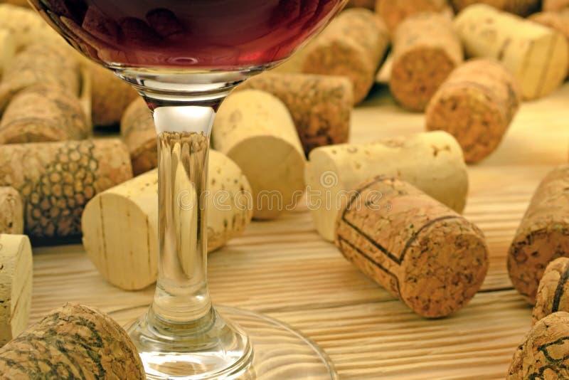 Exponeringsglas av vin på bakgrundskorkar royaltyfria bilder