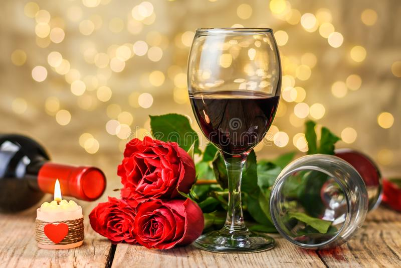 Exponeringsglas av vin, rosor och den brännande stearinljuset arkivbild