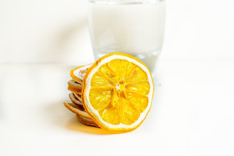 Exponeringsglas av vit bakgrund för vatten med den torkade citronskivan i bakgrunden Slut som skjutas upp royaltyfria foton