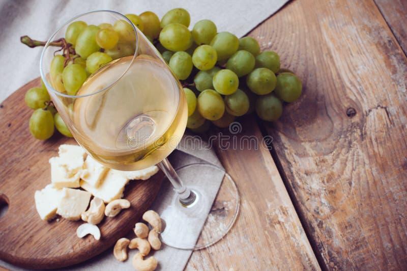 Exponeringsglas av vitt vin, druvor, kasjuer och mjuk ost arkivfoto