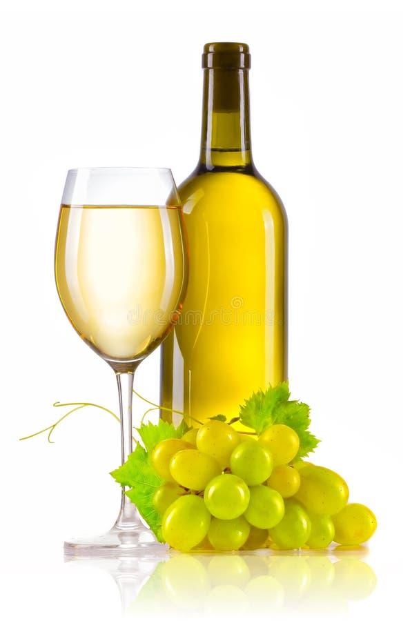 Exponeringsglas av vitt vin med den isolerade flaskan och mogna druvor royaltyfri bild