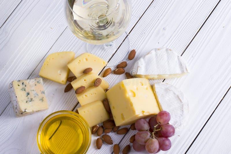 Exponeringsglas av vitt vin med mellanmål - olika typer av ost, fikonträd, muttrar, honung, druvor på en träbrädebakgrund arkivbilder