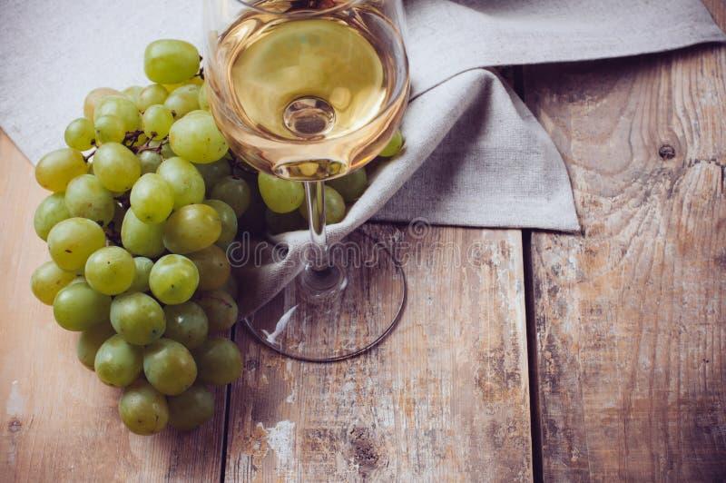 Exponeringsglas av vitt vin och druvor arkivfoto