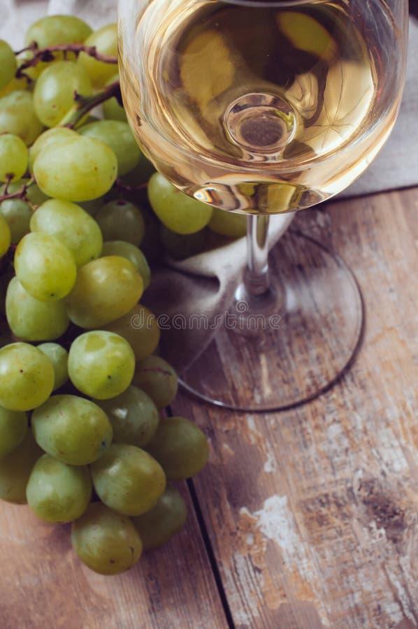 Exponeringsglas av vitt vin och druvor fotografering för bildbyråer