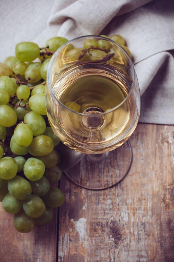 Exponeringsglas av vitt vin och druvor arkivbild