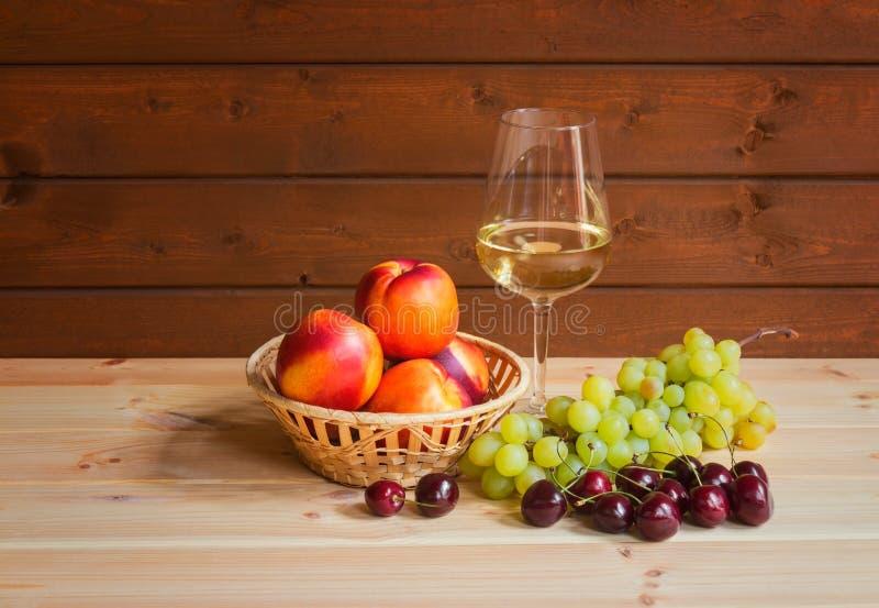 Exponeringsglas av vitt vin och nya mogna frukter på trätabellen arkivfoto