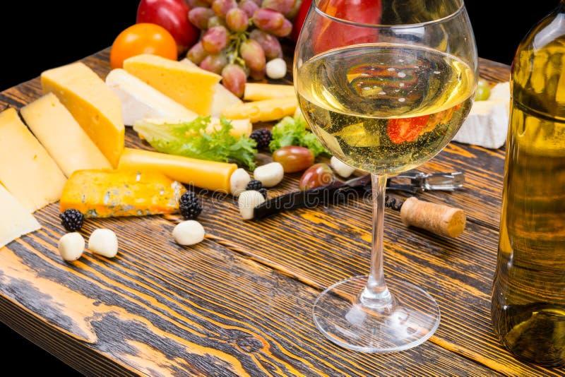 Exponeringsglas av vitt vin på tabellen med ost och frukt arkivfoton