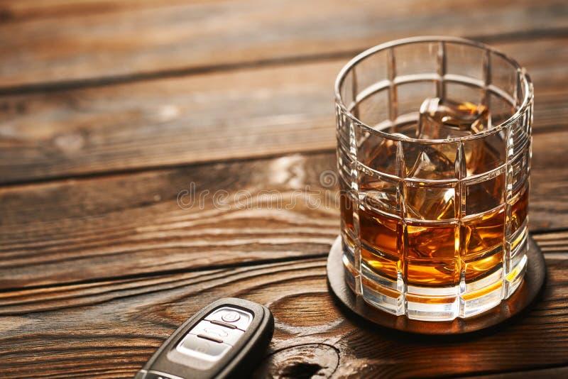 Exponeringsglas av whisky- eller alkoholdrinken med tangent för iskuber och bil Drink- och drevbegrepp arkivbilder