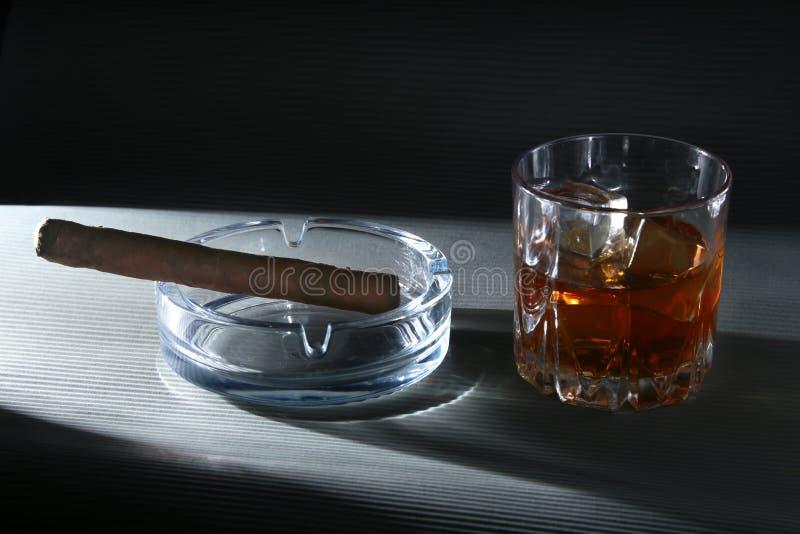 Exponeringsglas av whisky eller bourbon med is och cigarren på den svarta stentabellen Selektivt fokusera fotografering för bildbyråer