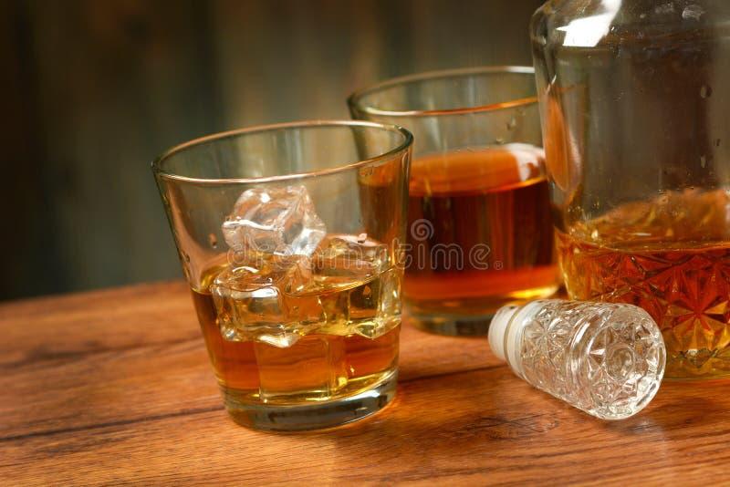 Exponeringsglas av whisky med is arkivfoto