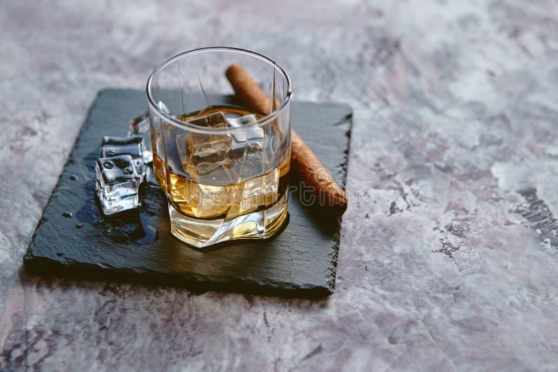 Exponeringsglas av whisky med den iskuber och cigarren royaltyfria foton