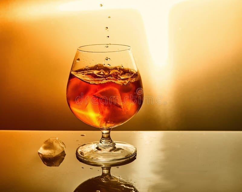Exponeringsglas av whisky med droppar och is p? en orange bakgrund arkivbild