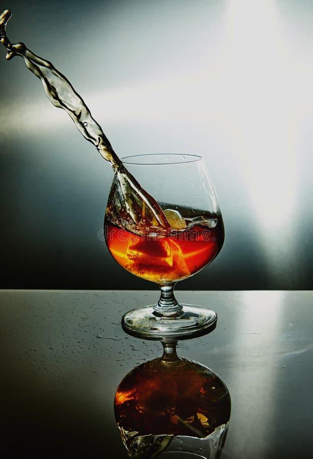 Exponeringsglas av whisky med en v?g p? en gr? bakgrund royaltyfri foto