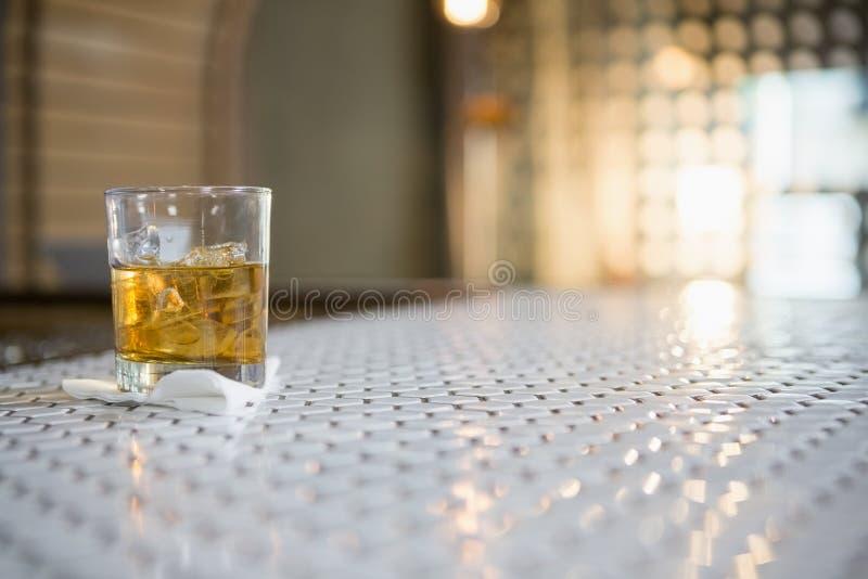 Exponeringsglas av whisky med iskuben på stångräknare arkivfoton