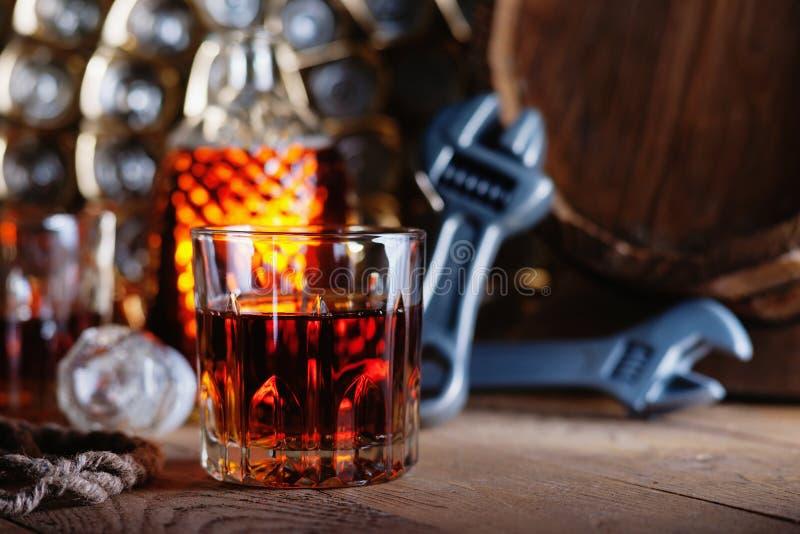 Exponeringsglas av whisky med justerbara skiftnycklar och trätrumman arkivfoton