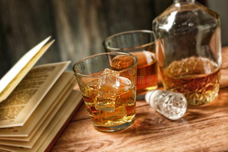 Exponeringsglas av whisky med is och öppnar boken - selektiv fokus royaltyfri bild