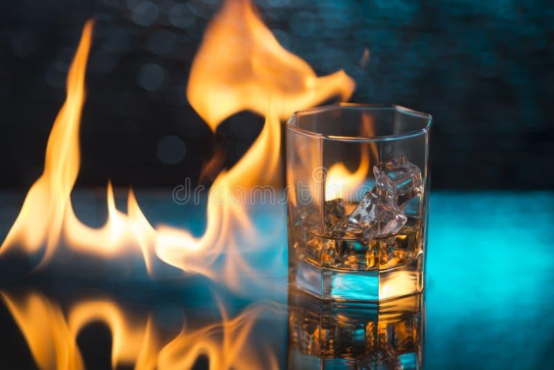 Exponeringsglas av whisky med is på en blå bakgrund och brand flammar royaltyfria bilder