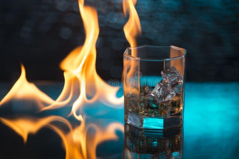 Exponeringsglas av whisky med is på en blå bakgrund och brand flammar royaltyfria foton