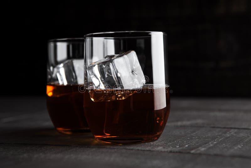 Exponeringsglas av whisky med is på träbakgrund royaltyfria foton