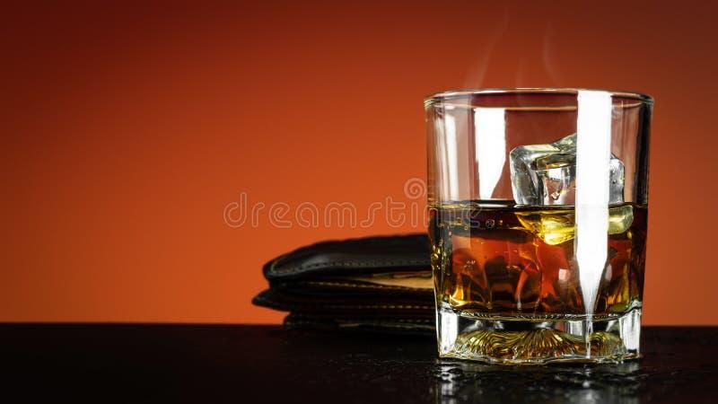 Exponeringsglas av whisky- och iskuben på röd bakgrunds- och kylarök Whiskyexponeringsglas- och handväskapåse i berusat begrepp royaltyfria foton