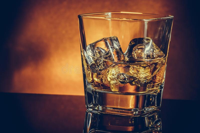 Exponeringsglas av whisky på den svarta tabellen med reflexionen och guldbakgrund, varm atmosfär arkivfoton