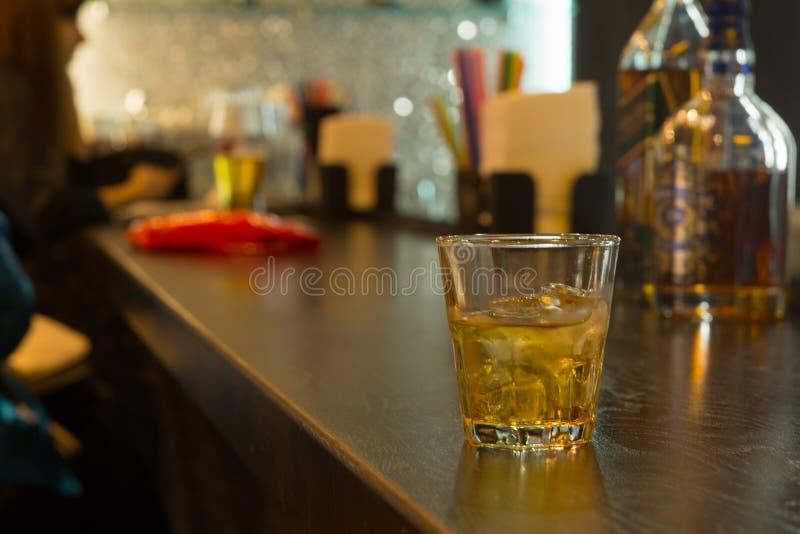 Exponeringsglas av whisky på is på en stångräknare royaltyfri fotografi