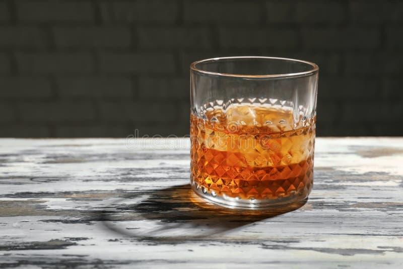 Exponeringsglas av whisky p? tr?tabellen arkivfoto
