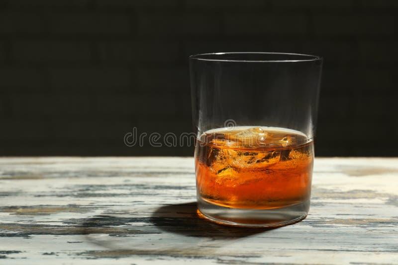 Exponeringsglas av whisky p? tr?tabellen arkivbild