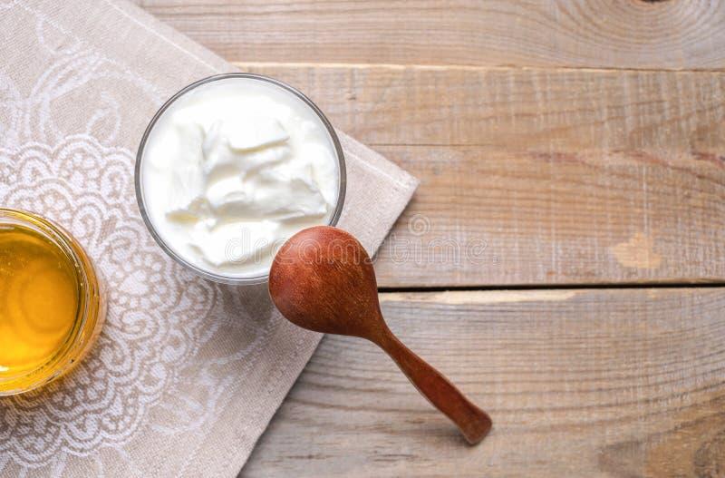 Exponeringsglas av yoghurten, träskeden och kruset av honung på trätabellen arkivbilder