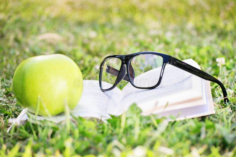 Exponeringsglas, bok och äpple på ett grönt gräs royaltyfria foton