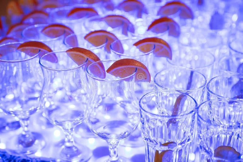 Exponeringsglas för alkoholdrycker med citronen på tabellen, blått ljus fotografering för bildbyråer