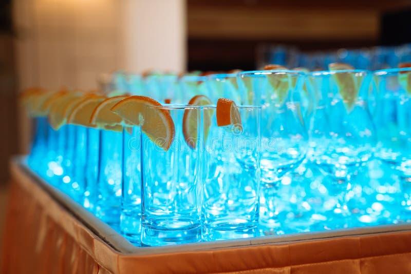 Exponeringsglas för alkoholdrycker med citronen på tabellen, blått ljus royaltyfria foton