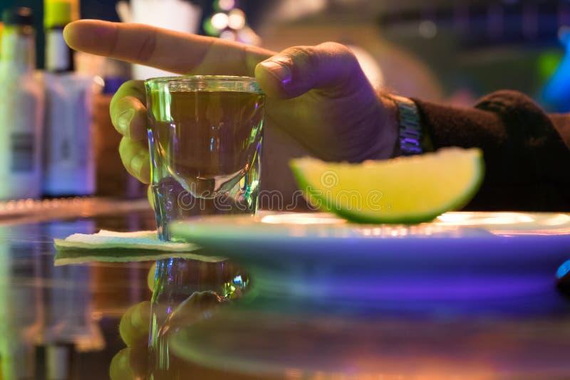 Exponeringsglas för hand för man` s hållande av tequila eller vodka på stång Närliggande är plattan med limefruktskivan Neonbelys arkivbild